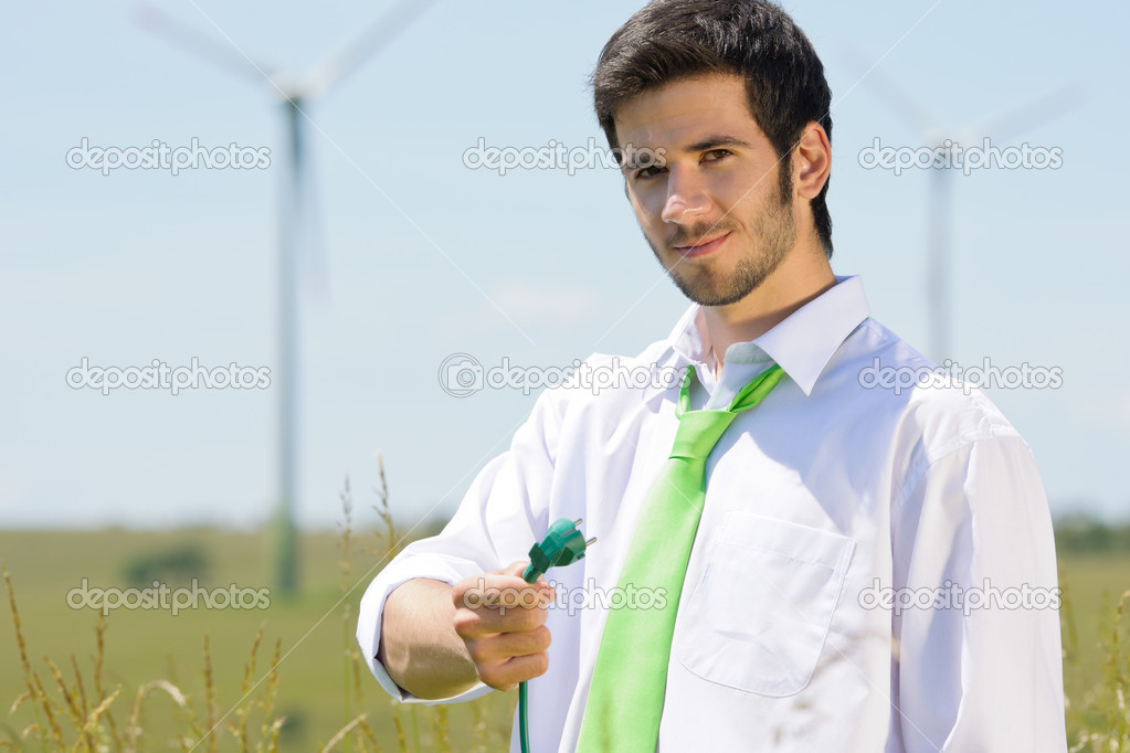 Green energy - young businessman hold plug in field with windmill