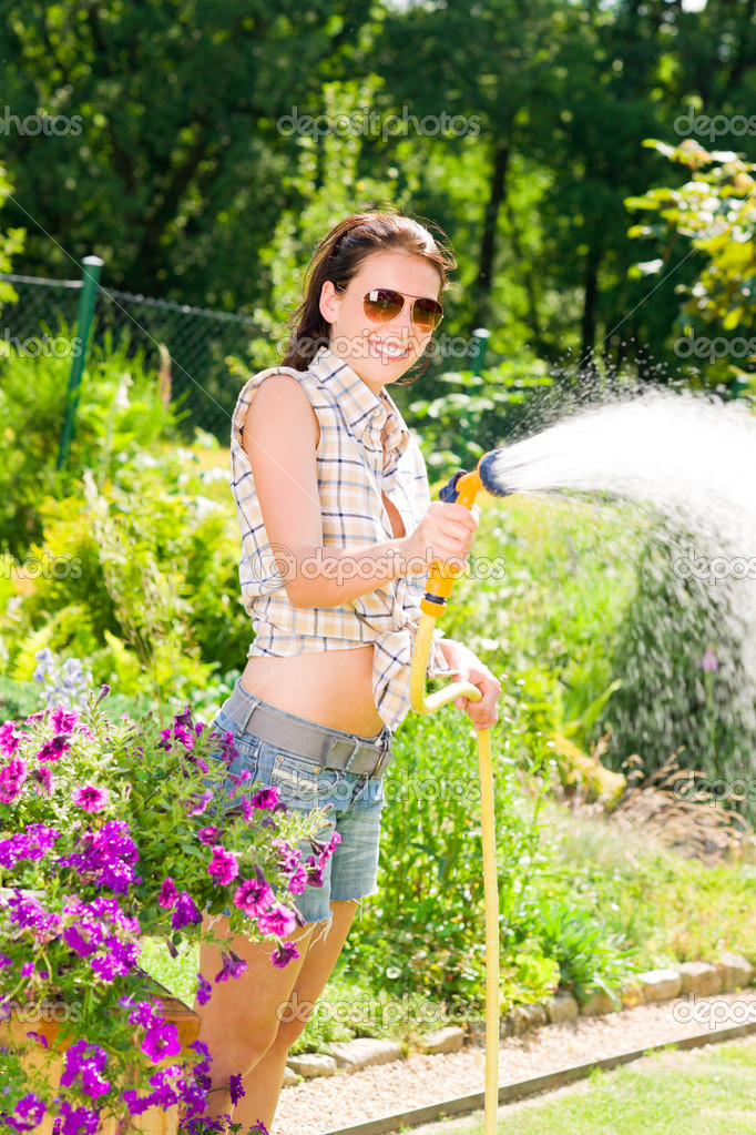 Summer garden smiling woman watering hose flower sunny day