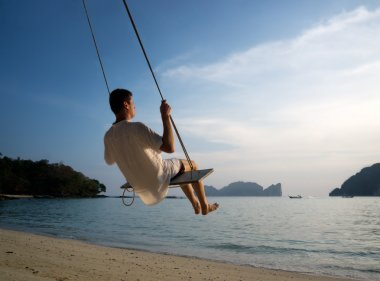 Young man on beach swing Phi Phi Thailand