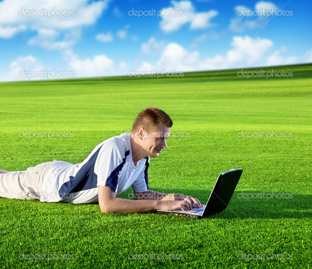 Young man use a notebook on green field