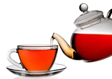 Tea being poured into glass tea cup isolated on a white backgrou