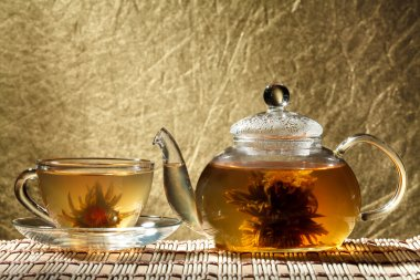 Glass teapot and a cup of green tea on a gold background