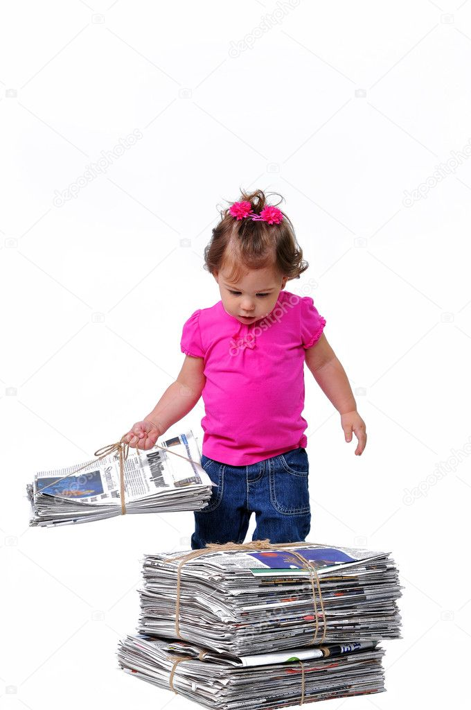 Toddler holging a stack of newspaper for recycling