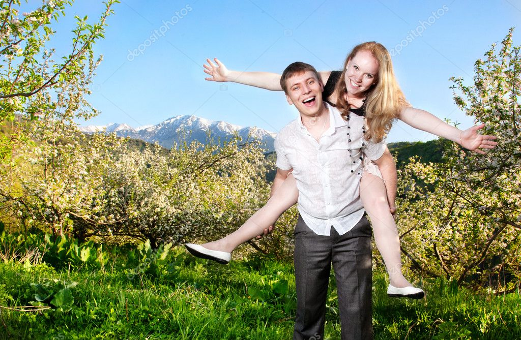 Couple having fun around bloomy trees