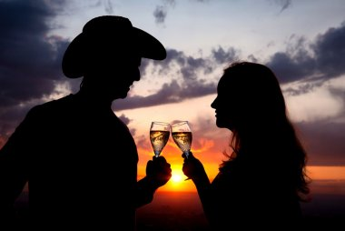 Couple Silhouettes clanging glasses at sunset
