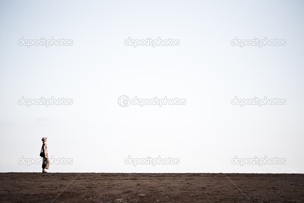 Woman walking on the black sand stock vector