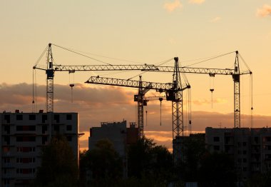 Cranes on construction site house at sunset