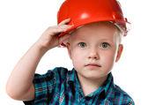 Fotografie kleiner Junge in einen roten Bau-Helm