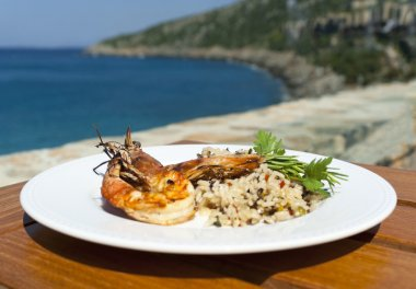 The dish with srimps and rice near mediterranean shore.