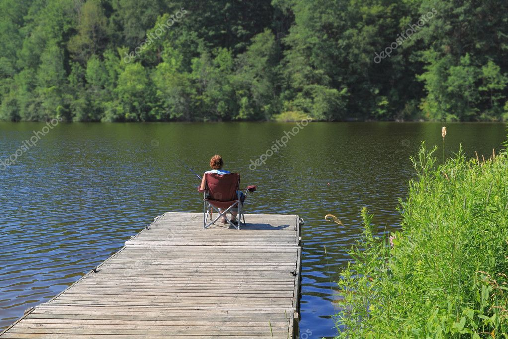Picture of morning fishing in the lake from the dock. Elderly woman fishes early morning in the lake from the dock (pier) in front of her house. stock vector
