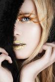 Fotografie Blattgold und falsche Wimpern auf einer blonden Frau
