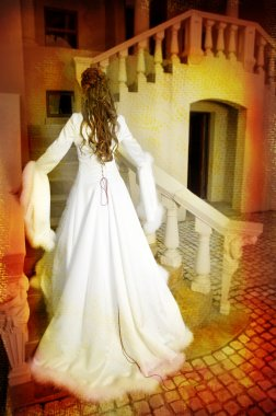 Beautiful bride in long silk coat on staircase