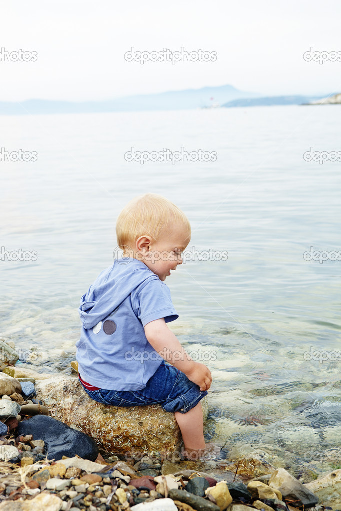 Little blond one year old boy sitting on a rock