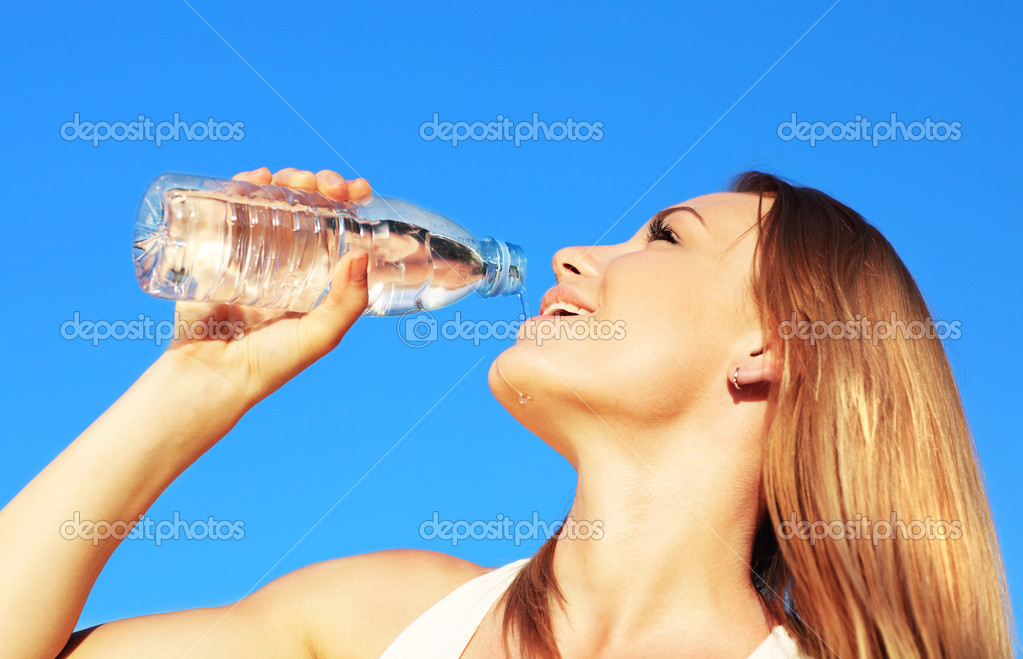 Beautiful female drinking water over blue sky background