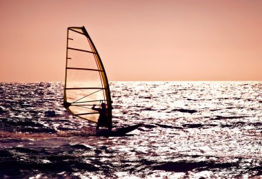 Windsurfer silhouette over sea sunset