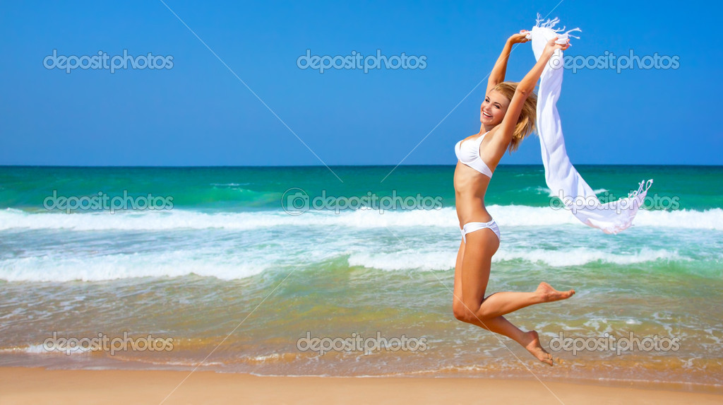 Jumping happy girl on the beach
