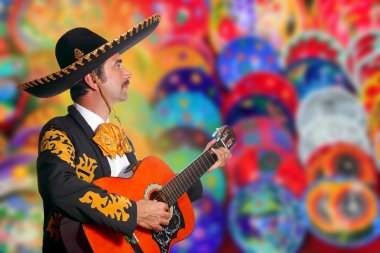 Charro Mariachi playing guitar over colorful blur