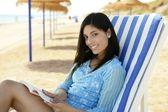 Fotografie schöne Frau mit einem Buch entspannt am Strand