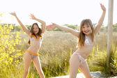 dívky tančí venku v parku v bikinách