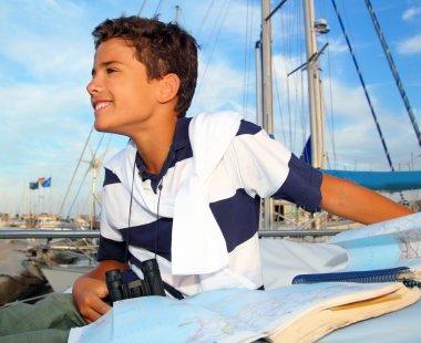 Boy teen sailorsitting on marina boat chart map