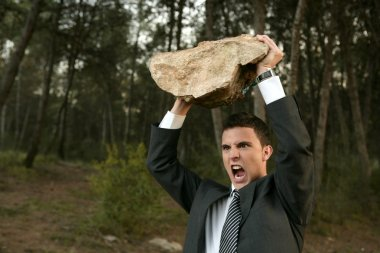 Angry businessman outdoor, big stone in hands
