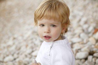 Boy portrait winter outdoor, stones background