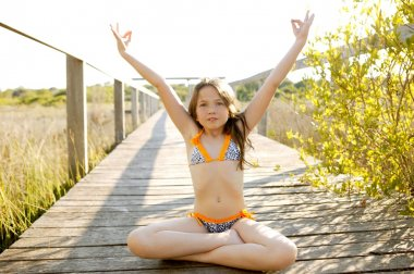 Beautiful relaxed zen teen meditation in bikini