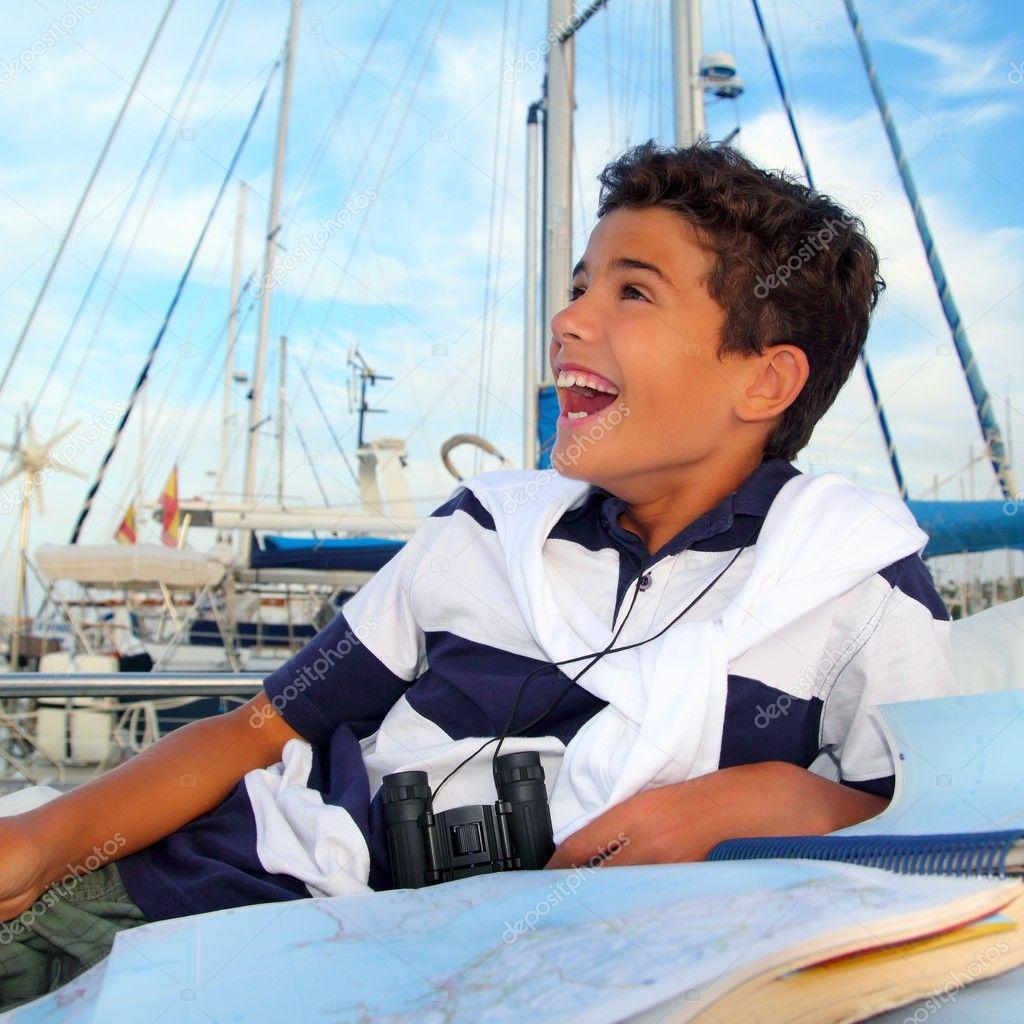 Boy teen sailor laying on marina boat chart map