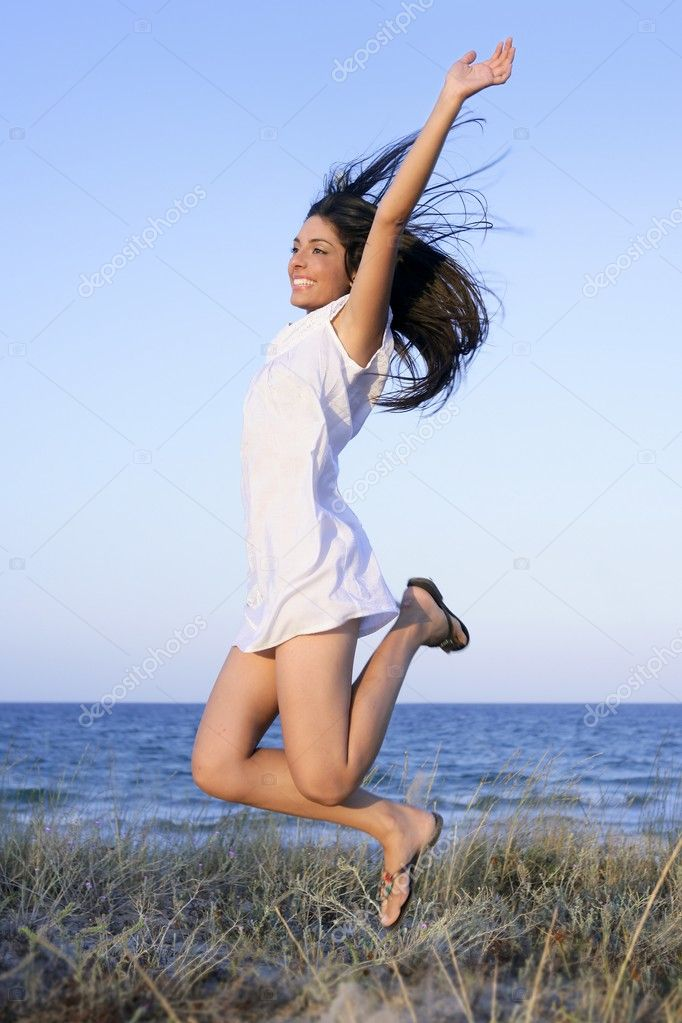 Beautiful brunette jumping in the beach