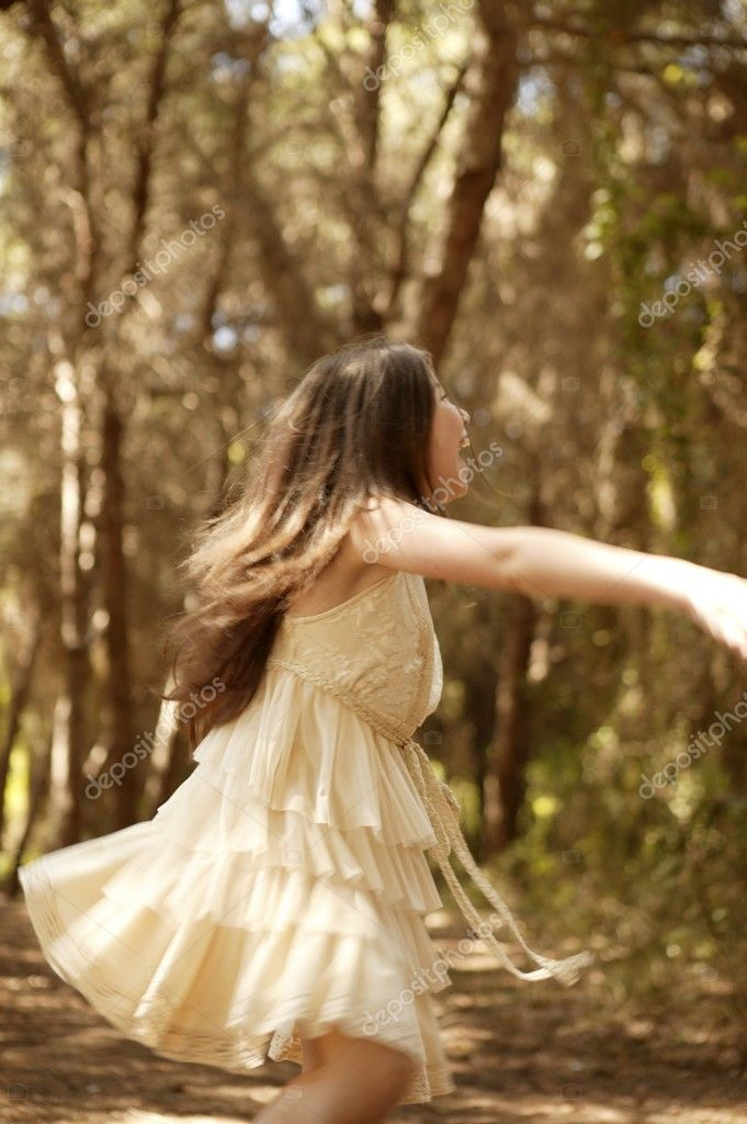 Teen girl dancing in the brown pine forest