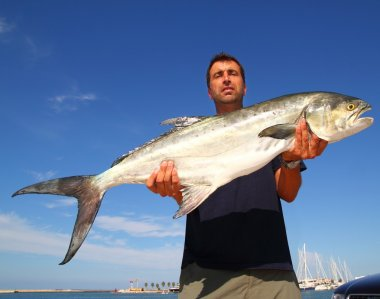 Fisherman holding catch Garrick Lichia Amia