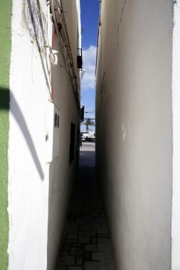 Extremely narrow street, white walls, blue sky