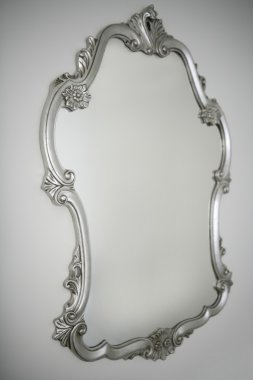 Baroque silver mirror over white wall