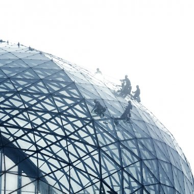 Workers cleaning a round glass facade
