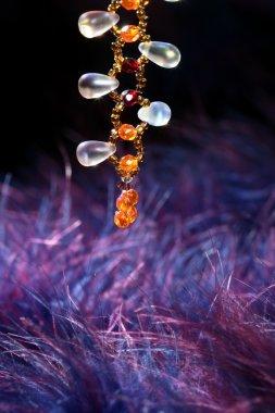 Orange jewel necklace over blue purple feather