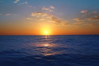 Sunrise sunset in ocean blue sea glowing sun