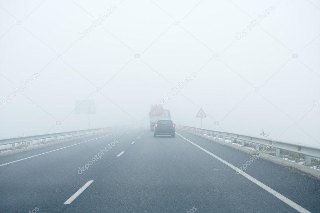 Фотообои Foggy gray road, cars driving into the fog