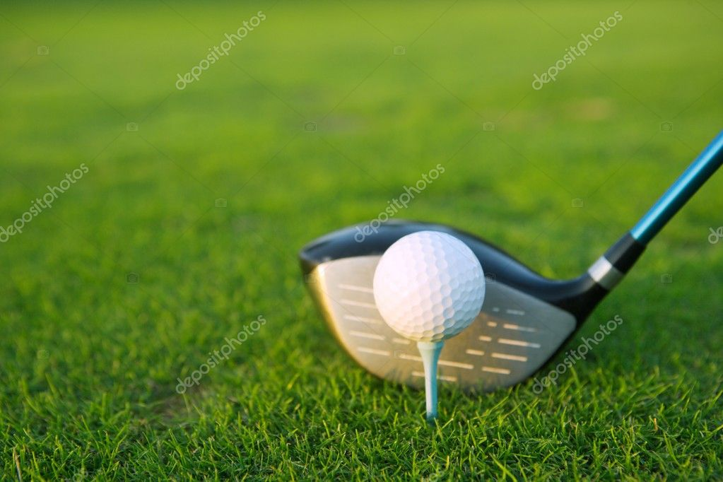 Golf tee ball club driver in green grass course