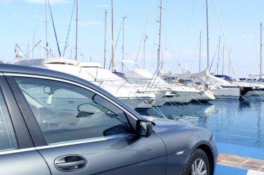 Luxury car and yacht sailboats on Spain marina