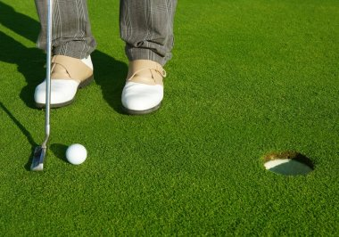 Golf green hole course man putting short ball