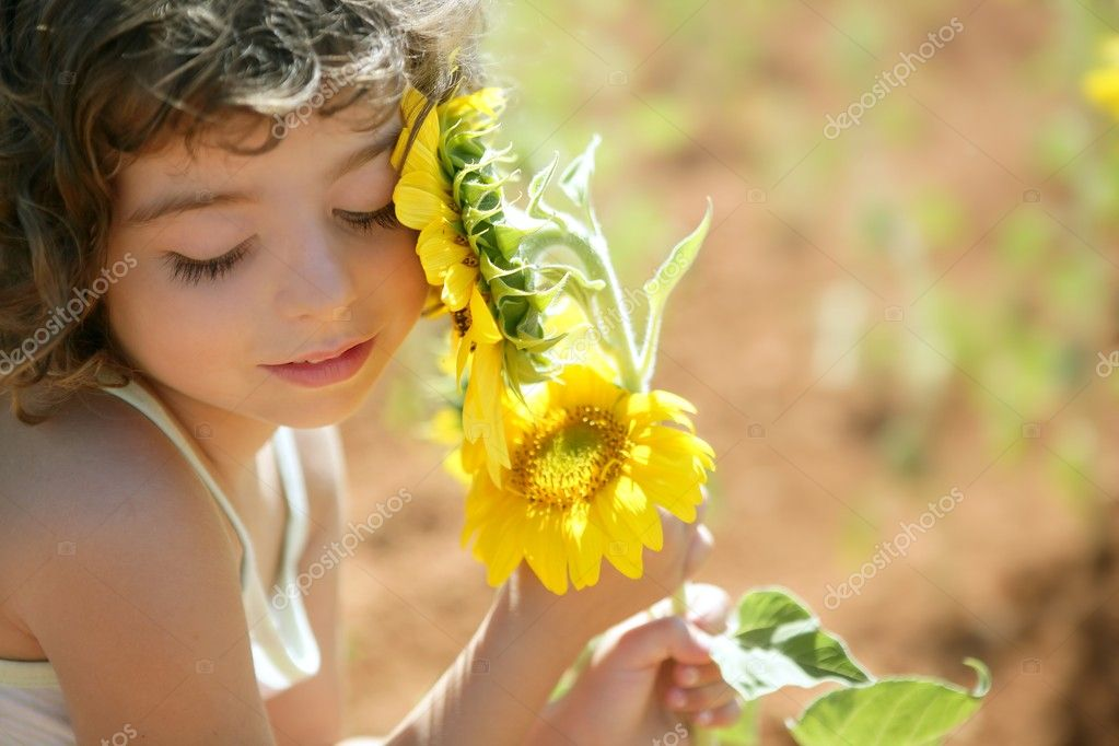 Beautiful little girl in a summer sunflower field