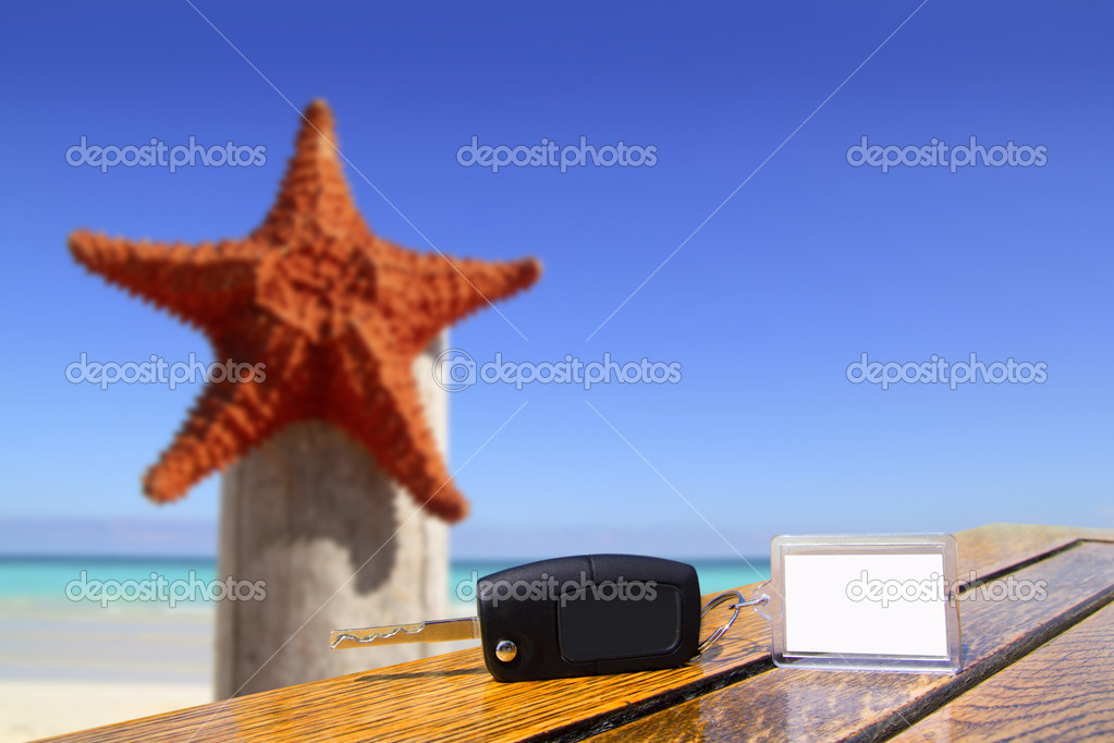 Car rental keys on wood table in vacation with starfish