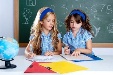 Kids students in classroom helping each other