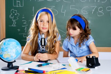 Children girls at school classroom with microscope