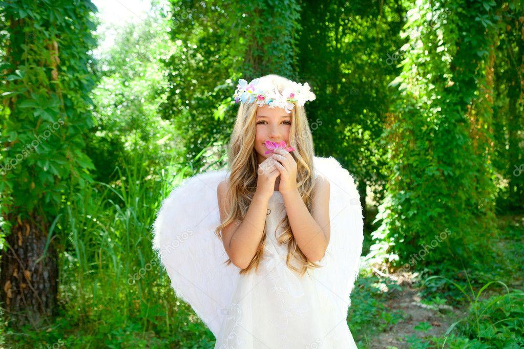 Angel children girl smelling pinks flower in forest