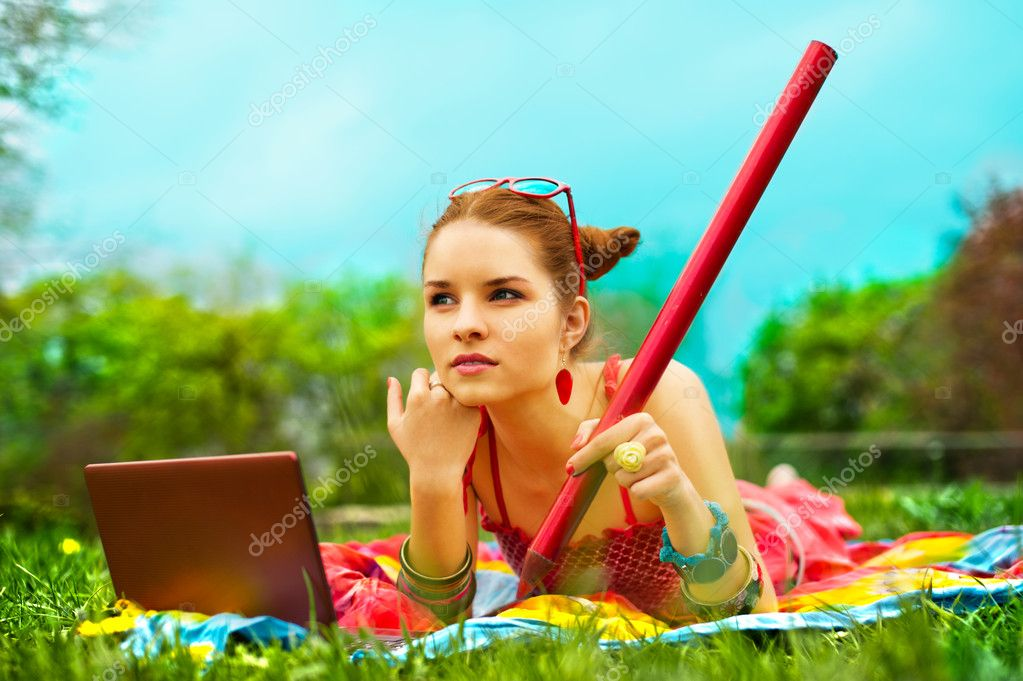 Beautiful young woman with laptop and pencil on green grass