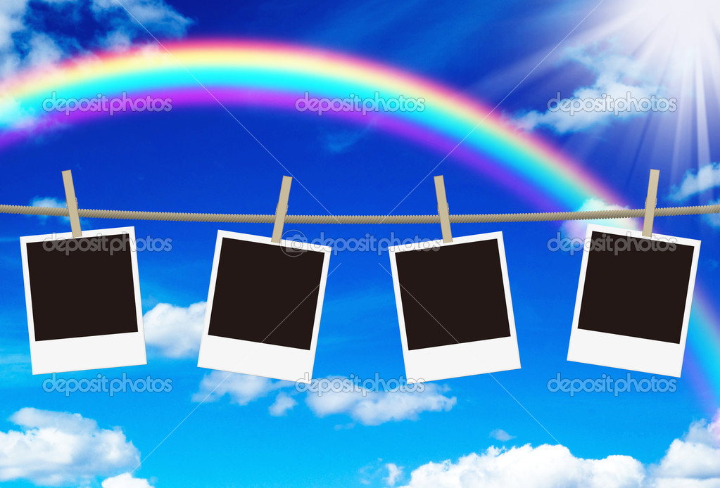 Blank photo frames hanging against rainbow sky