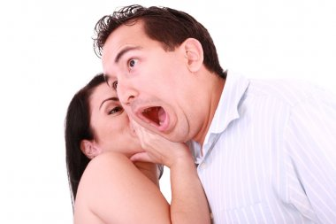 Woman tells something into surprised guy's ear isolated on white