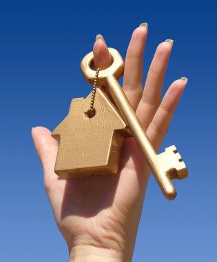 Hand holding golden key.