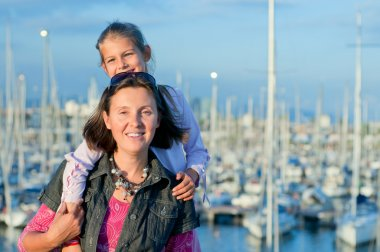 Portrait of a girl with her mother near yachts